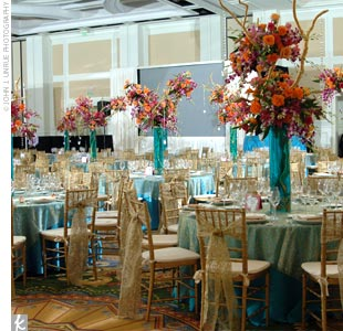 Joy and Sateesh's reception tables were topped with four-foot-high centerpieces of orchids and roses adorned with crystals. The pink, orange, and fuchsia blooms sat in tall turquoise cylinders etched in gold with the filigree pattern from the wedding invites.