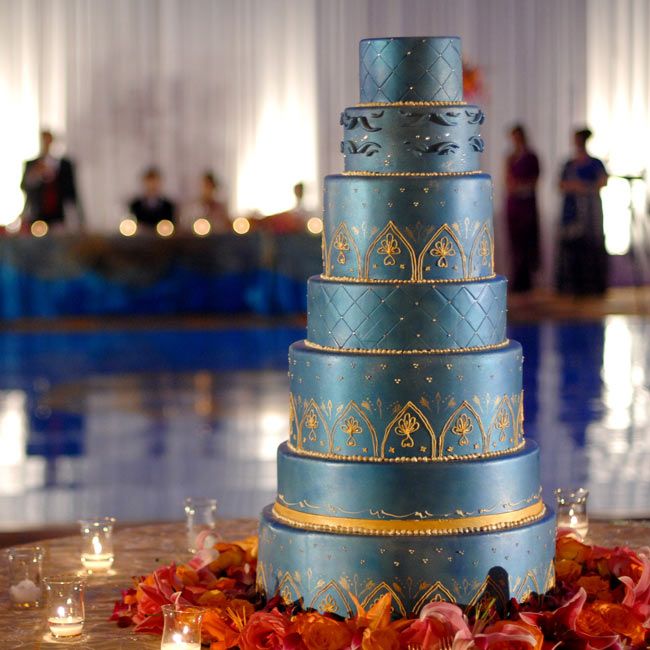 Joy and Sateesh cut into a seven-tiered cake custom-designed in turquoise and gold to match their invitations.