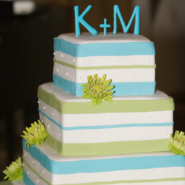 The vibrant aqua and green-striped cake was accented with sugar button mums and topped with the couple's monogram.