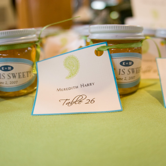 "Tiny jars of honey doubled as place cards, displaying each guest's name, table number, and the motto ""Life is Sweet!"""