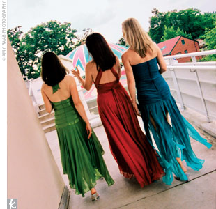 Renees three bridesmaids each wore a different dress by BCBG in the weddings bold colors -- one orange, one blue, and one in green.