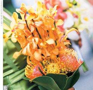Renee&#39;s bridesmaids carried bouquets of orchids in bright colors, such as yellow, pink, and orange.