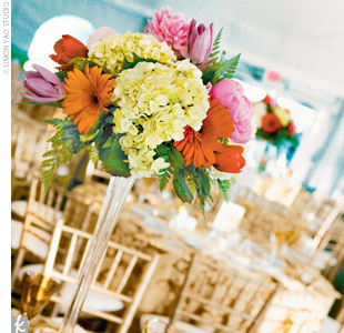 Dramatic Eiffel Tower vases were filled with clusters of bright hydrangeas, tulips, lilies, peonies, and daisies. The colorful arrangements played off the gold place settings and elegant, gold damask linens.