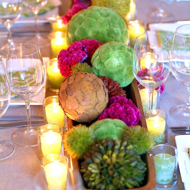 Wooden troughs filled with spheres of dried flowers and herbs topped off the reception tables, with pink cockscomb mixed in for a pop of color. Cylindrical arrangements -- including curly willow, faux chestnut branches, dahlias, and hypericum berries -- were also set up on the tables.