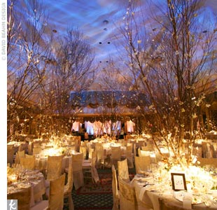 Once guests picked up their escort cards, they headed into a winter wonderland where towering trees seemed to grow out of each reception table. For dramatic yet romantic mood lighting, hundreds of candles were arranged on the tables. Even the linens shined brightly; the tablecloths, napkins, and crushed velvet chair covers were embroidered with whi ...