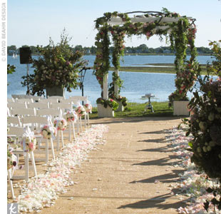 For a bayside ceremony in Westport, Connecticut, David and his team built an arbor and covered it in grapevine for an organic look. Pomanders of various pink and white roses hung from each end chair, while hundreds of petals lined both sides of the aisle. 