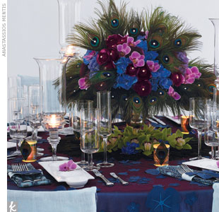 For a photo shoot for The Knot, David created a layered look using a tablecloth that gives the impression of flowers floating in a pond, adding to the tablescape's overall tranquility. Tall hurricanes reflect lots of candlelight, while a centerpiece of dark peacock feathers tops off the look.