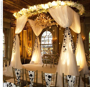 When a bride fell in love with a floral-embroidered fabric, David used the material as sashes on the ceremony chairs and huppah for a stylish hint of black and white. Roses and hydrangeas created a border around the top of the huppah.
