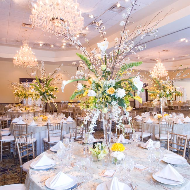 Gold table linens and arrangements of white, yellow, and green flowers were chosen to complement the ballroom's yellow walls. Tall arrangements of flowering branches were softened with orchids, spray roses, ranunculus, and hydrangea.