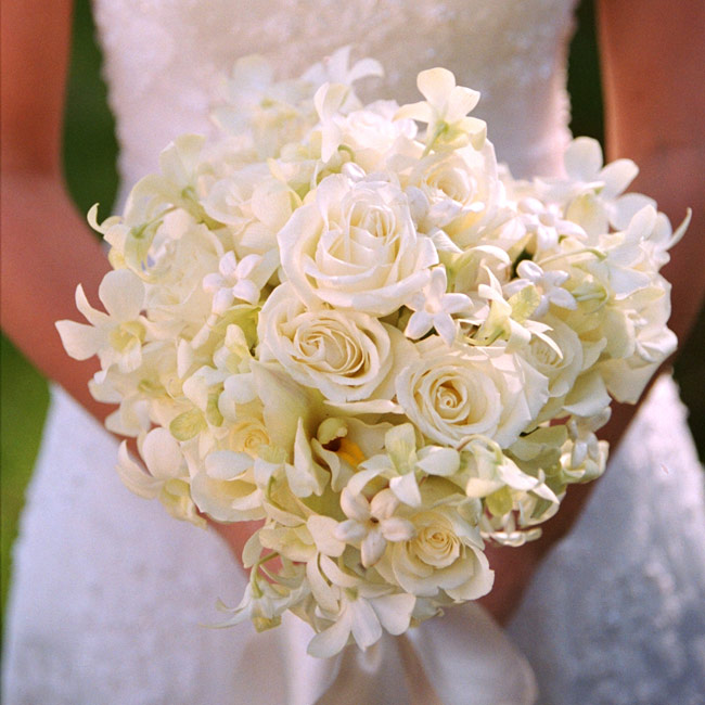 Danielle carried a round cluster of ivory roses, white dendrobium orchids, light green cymbidium orchids, and stephanotis. The stems were tied together in a loose, white satin ribbon.