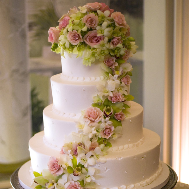 The four-tiered cake was covered with delicious buttercream and decorated with pink and green roses, hydrangeas, and orchids. The inside was black velvet and red velvet cake with raspberry jam and white ganache.