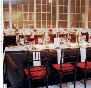 "Sam and Jack strung the exposed ceiling pipes with antiqued glass votives and crystals to create a romantic-yet-modern shimmer effect. They cleverly placed the long tables in multiple directions to prevent a ""cafeteria"" feel. An inky black hue gave the traditional ballroom chairs a hip feel suited to the loft setting."