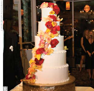 The five-tiered chocolate cake had raspberry filling and ivory-colored buttercream frosting. It was adorned with autumn-colored roses and calla lilies cascading down from the top.