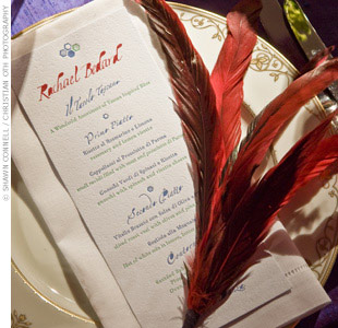 Red feathers added a dose of glamour to each guest&#39;s place setting. 