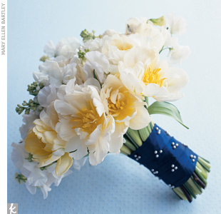 No matter what wedding style you've chosen, you should be able to find flowers that convey the right attitude (for example, lime green cymbidium orchids=exotic elegance). We stuck with a classic all-white bridal bouquet but chose a variety of blooms -- double Dutch tulips and sweet pea -- for textural interest. We wrapped it with a modern navy ribb ...