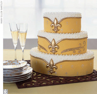 Theme #5: FlourishesThe best thing about a symbol-driven wedding? You can use the accent in unexpected places. Our cake baker covered a three-tiered oval-shaped cake with lemon buttercream and rolled fondant, white royal iced pearl dots, and gold fleur-de-lis molded sugar medallions. Gold Parisian Wallpaper dessert plates, Rosanna; champagne flutes ...