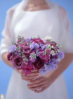 With ultra-vivid hues, this charming little cluster just might steal the show. The palette is achieved with deep lavender roses, lavender sweet peas, and stock in pinks and purples. Bonus: The roses and sweet peas have a heavenly fragrance.