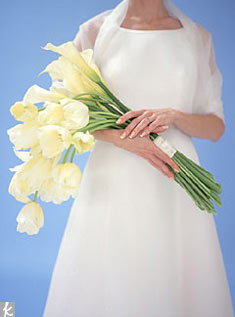 Carried in the arms like a beauty-queen prize (hence the name), the pageant bouquet takes a modern turn in this version of unadorned long-stemmed calla lilies and French tulips in creamy ivory. Bonus: Place the bare stems in water at your reception for an extra floral decoration, then enjoy the blooms at home after the wedding.