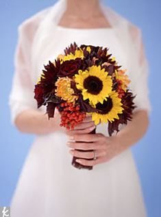 In this autumn mix, unconventional bridal blossoms like yellow and chocolate sunflowers mix with deep Black Magic roses; orange dahlias pull it all together. Bud bonus: using flowers in season helps cut costs. Photo: Paul Costello
