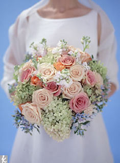 Even an armload of blooms can have a bridal look. Pee gee hydrangeas are a lovely, lacy accent to stock and pale blue tweedia; roses in a range of related hues (Sahara, Rustique, and peach) keep the color fresh. Photo: Paul Costello