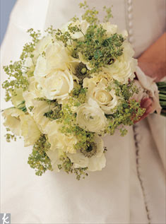 You can get a less formal feeling with a simple hand-tied bouquet of white roses, ranunculuses, and anemones mixed with the soft texture of green lady's mantle.