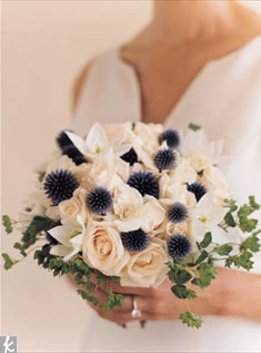 Spiky blue thistle poke their heads through a bountiful bed of white roses and gardenias.