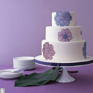 The new way to do flowers on your cake? Create a 3-D pattern. Pixilated cosmos piped on a three-tiered white fondant cake add a modern feel to a classic shape.