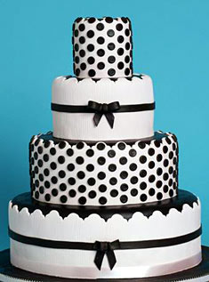 This four-tiered pale pink cake is trimmed with black frosted ribbon and dotted with chocolate buttons.