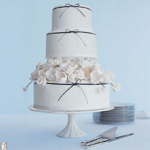 This white cake with white Swiss dots features a layer of all-white sugar flowers and a thin navy ribbon, which adds a touch of simple sophistication.