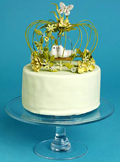 This mini-cake iced with lime-colored fondant is topped with a delicate birdcage decorated with butterflies and flowers.
