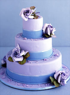 This three-tiered cake is wrapped in lavendar fondant and accented with blue piping and purple sugar roses.