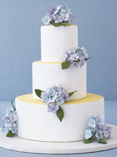 This three-tiered floral embossed fondant cake features clusters of sugar-paste hydrangeas.