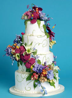 This classic four-tiered buttercream-frosted cake is draped with large, vibrant sugar flowers.