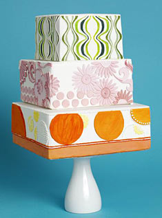 This three-tiered square fondant-frosted cake is decorated with fun patterns in bright orange, pink, and green.