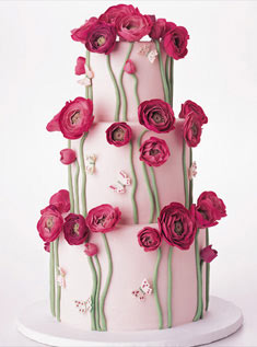 This three-tiered round cake is covered in pale pink fondant and adorned with long green fondant stems, gum paste hot pink ranunculus, and tiny butterflies.