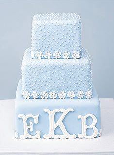 This three-tier stacked cake covered in baby blue fondant and adorned with sugar daisies features a classic sugar monogram.