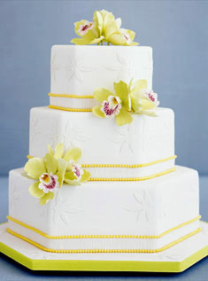 This three-tiered white hexagonal cake features raised floral appliques, a yellow-pearl trim, and sugar-paste green cymbidium orchids.