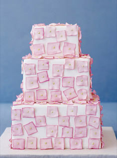 This three-tiered square cake iced with white fondant features sugar-paste pink squares dotted with sugar pearls.