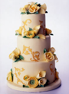 This three-tiered cake with gum paste roses, ranunculus, calla lilies, and lemon slices, features a Florentine-style hand-painted, gold scroll design.