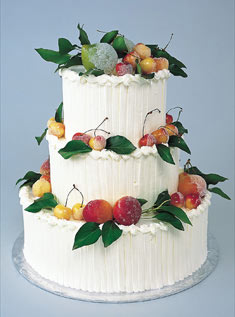 This three-tiered cake is covered in buttercream and adorned with sugared nectarines and cherries.