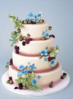 This four-tiered cake is topped with berries, sugar acorns, and sugar blue hydrangea.