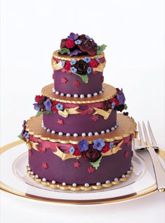 This individual dessert cake wrapped in purple fondant is decorated with hand-molded sugar flowers and gold ribbon accents.