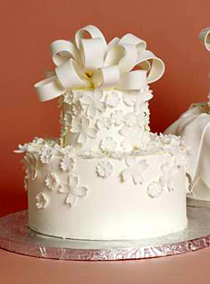 This mini two-tiered cake in creamy fondant is accented with tiny flowers and topped with a big frosted bow.