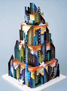 This four-tiered white cake is artfully decorated with colored-chocolate pieces to resemble a city skyline.