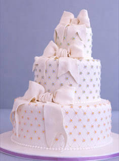 This three-tiered off-kilter cake is playfully dotted with sugar beads and fondant bows.