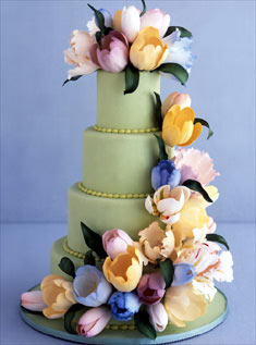 This four-tiered cake covered in green fondant is wrapped in a cascade of lush and lovely tulips.