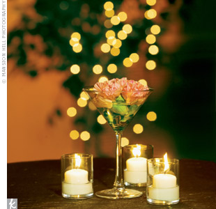 Martini glasses served as elegant vases for carnation blooms. White votive candles helped soften the look.