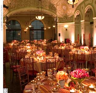For the dinner portion of an Indian wedding, Marina changed the color palette from peacock green to bright orange and red, reflective of the ceremony's color scheme. Sheer, sari fabric in bright orange was covered with a gold overlay to create a shimmering effect on the tables. For the centerpieces, Marina color-blocked the arrangements by using ca ...