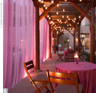 Following a two-hour Indian ceremony, which took place at dusk, guests moved onto a pink-saturated patio, draped with fabric and strung with votive candles that created a warm, romantic feel.
