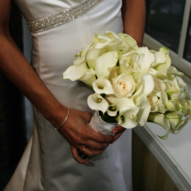 "Pam held a white bouquet filled with two of her favorite flowers: roses and calla lilies. ""The calla lilies are modern and fresh-looking, while the roses are elegant and traditional. Together, it made for a modern and elegant bouquet, the overall look I strove for throughout the wedding,"" Pam says."
